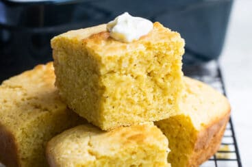 Four pieces of cornbread on a cooling rack.