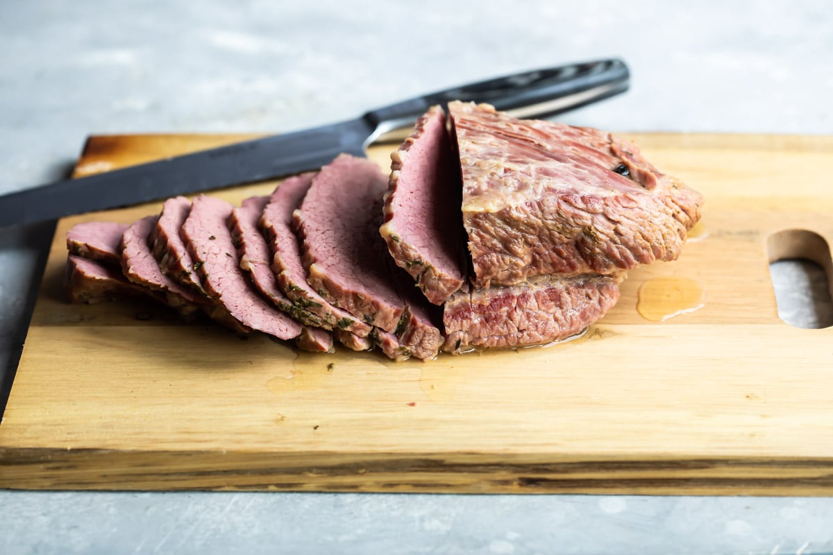 Corned beef sliced on a cutting board.