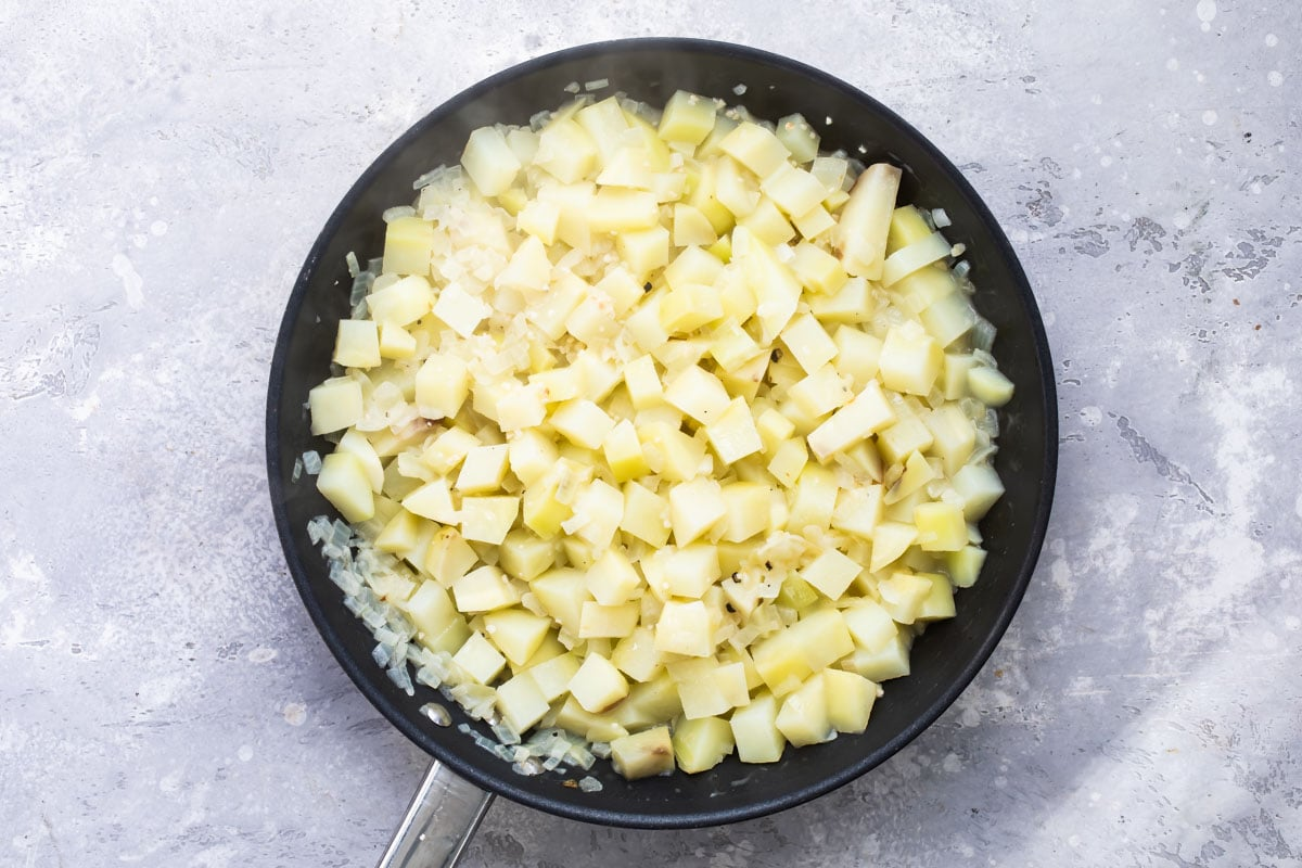 Potatoes cooking in a skillet.
