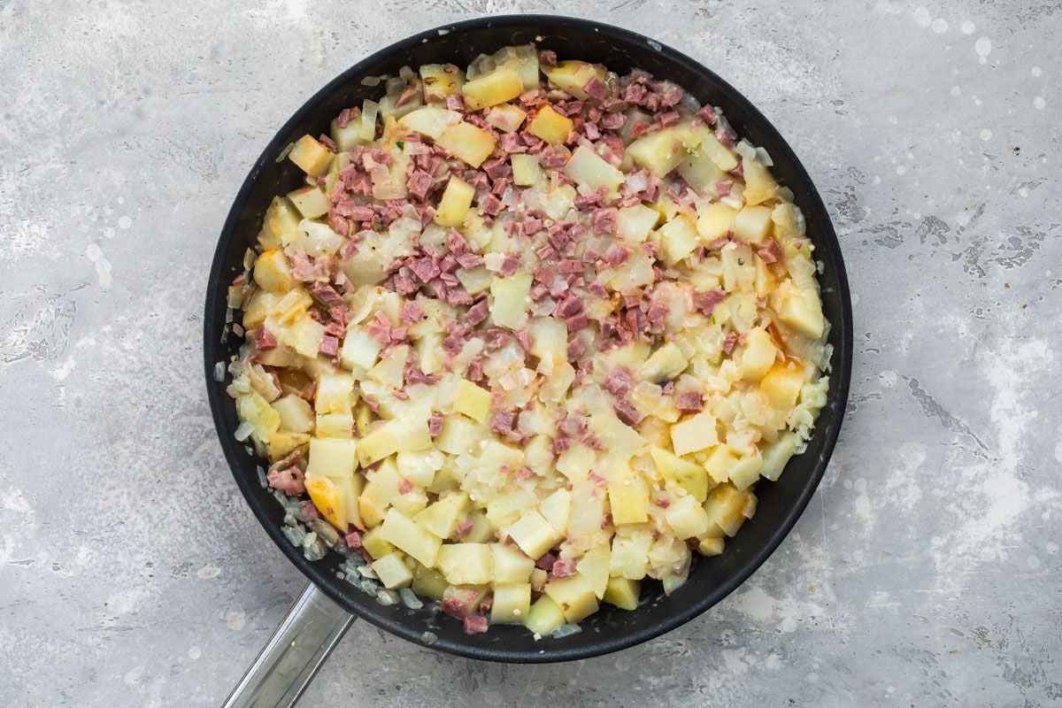Corned beef hash cooking in a skillet.