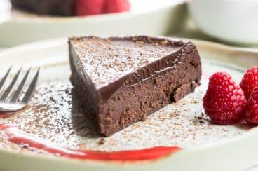 Flourless chocolate cake slice on a white plate.