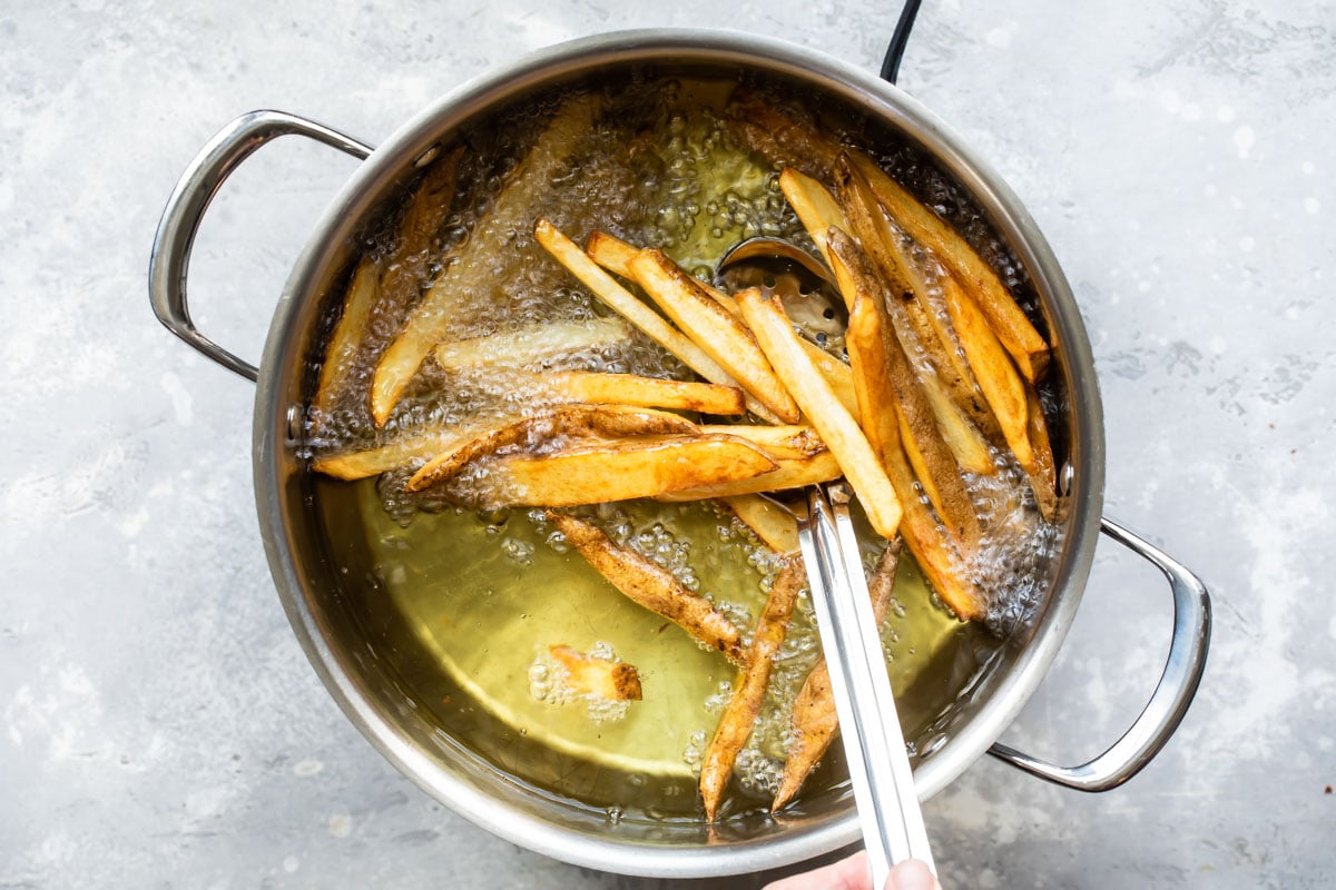Homemade French fries frying in oil.