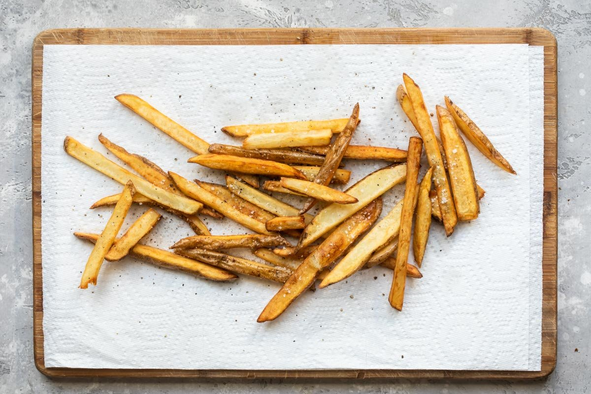 Homemade French fries draining on paper towels.