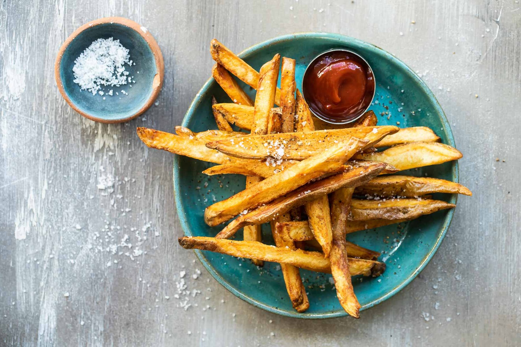 Homemade French fries on a teal plate with ketchup.