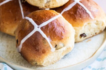 Hot cross buns on a gray platter.