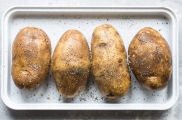 Four whole baked potatoes on a silver baking sheet.