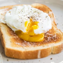 A poached egg on a slice of white toast.