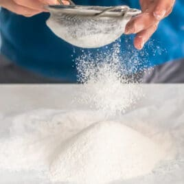 Flour being sifted onto parchment paper.