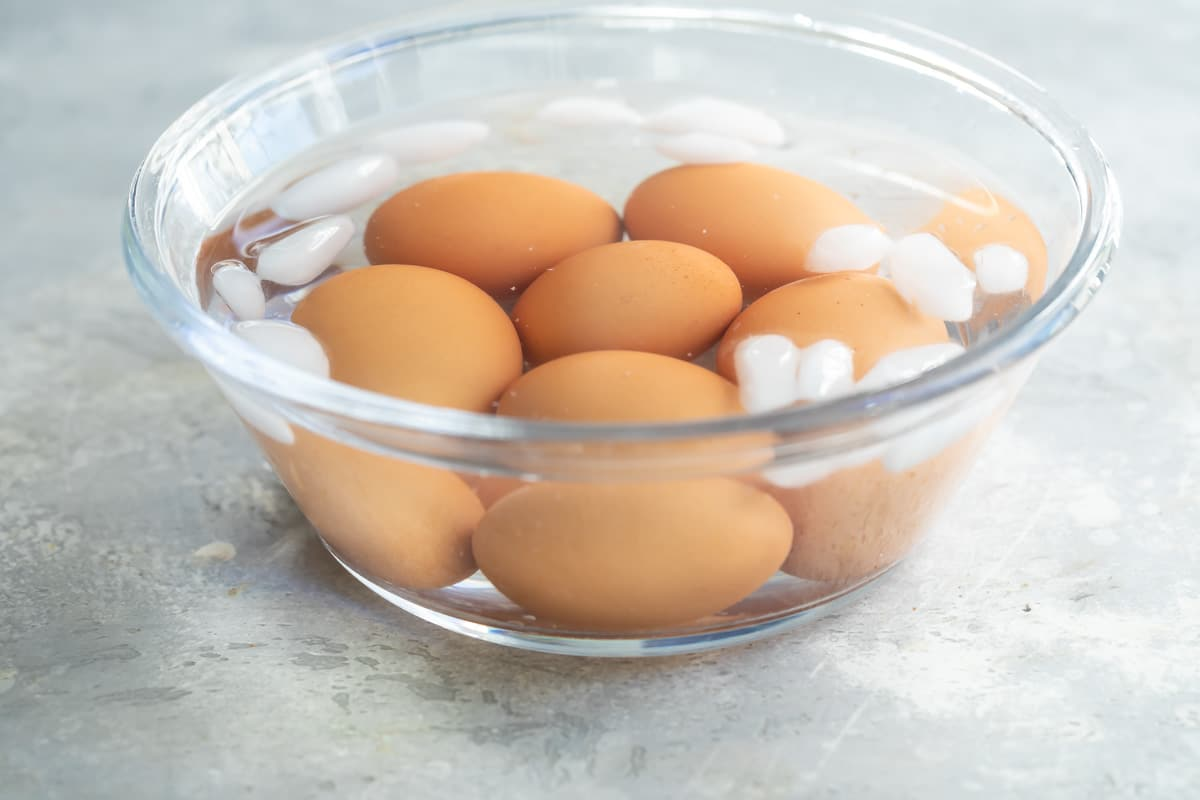 Soft boiled eggs cooling in an ice bath.