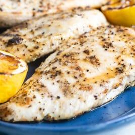 Lemon pepper chicken on a blue platter.