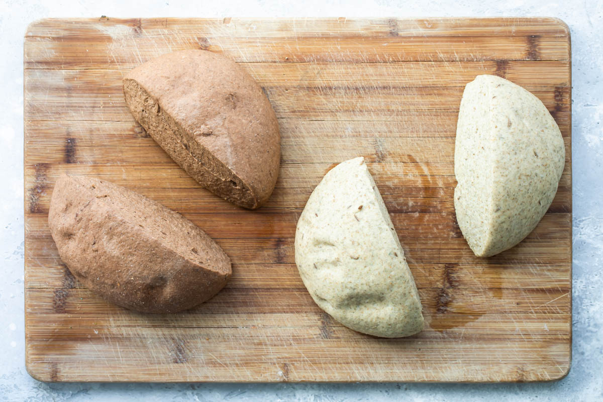 Two rounds of bread dough cut in half.