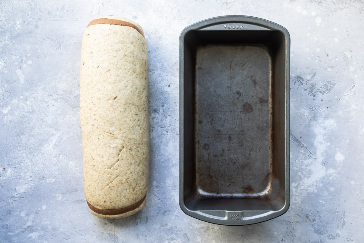 Unbaked bread next to a loaf pan.