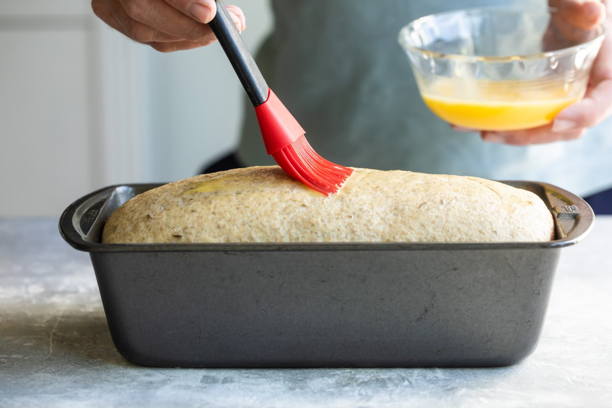 Brushing a loaf of bread with melted butter.