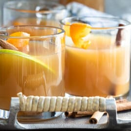 Three glasses of mulled cider on a silver serving platter.