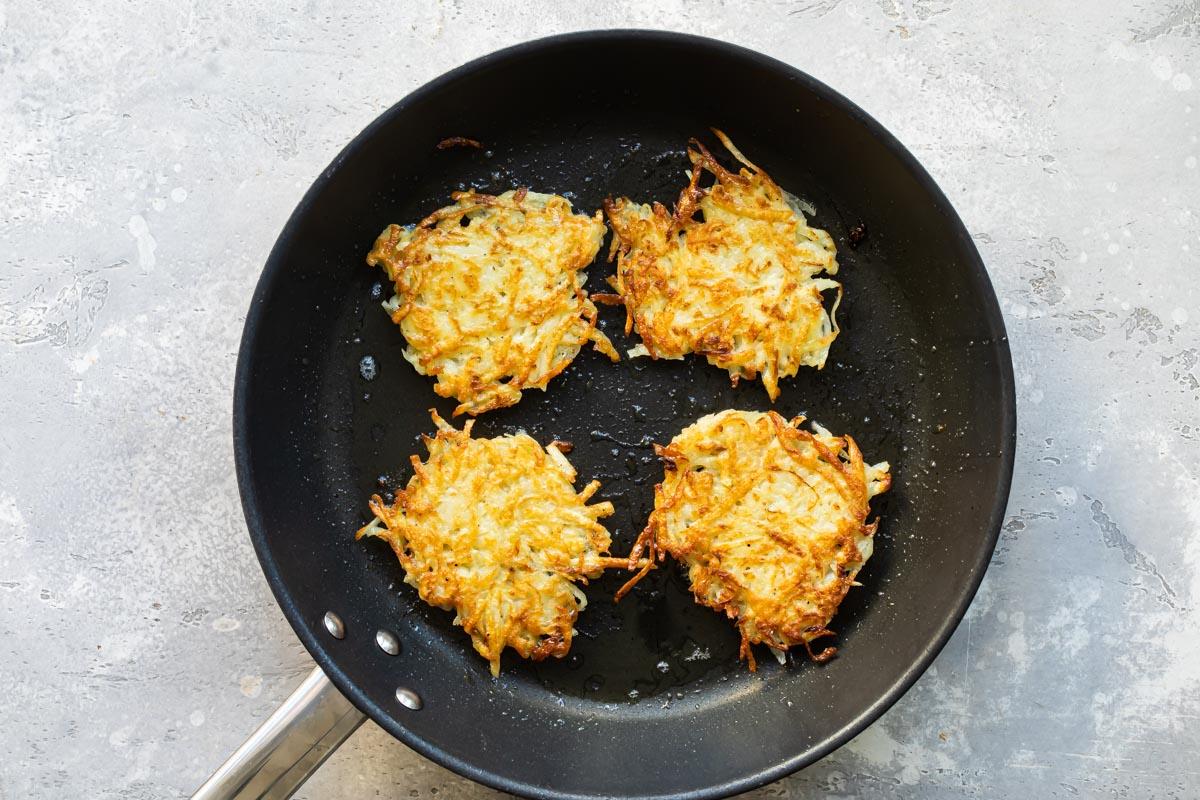 4 potato latkes frying in a pan.