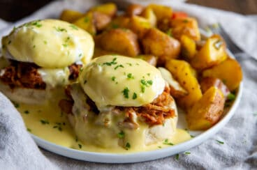 Pulled pork eggs benedict with a side of breakfast potatoes.