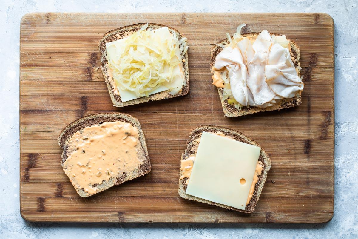 Assembling a rachel sandwich on a cutting board.