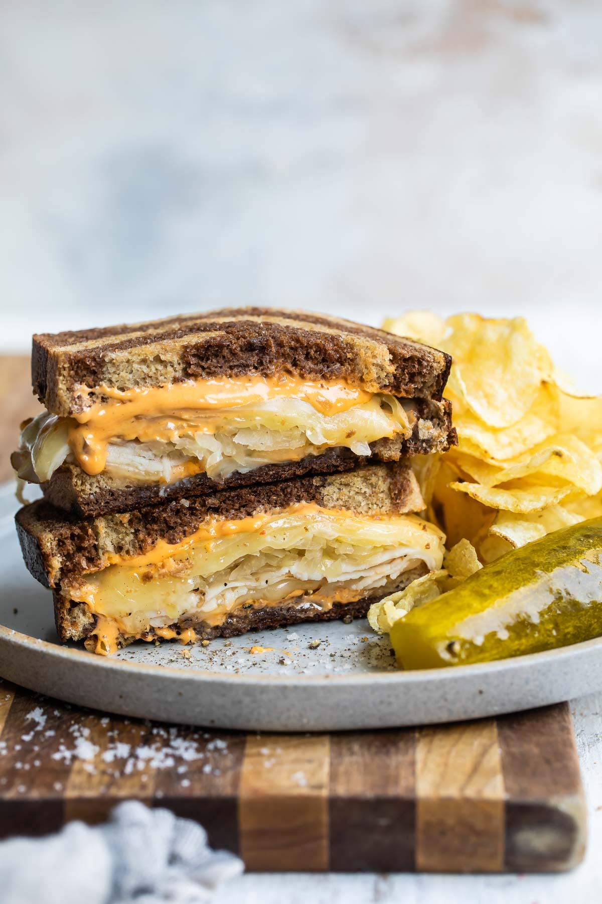 A rachel sandwich on a gray plate with a pickle spear and potato chips.