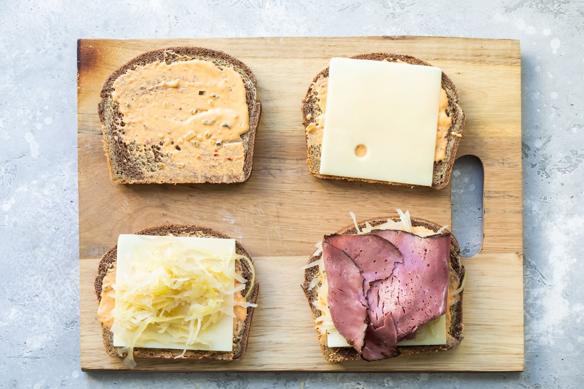 The stages of building a reuben sandwich.