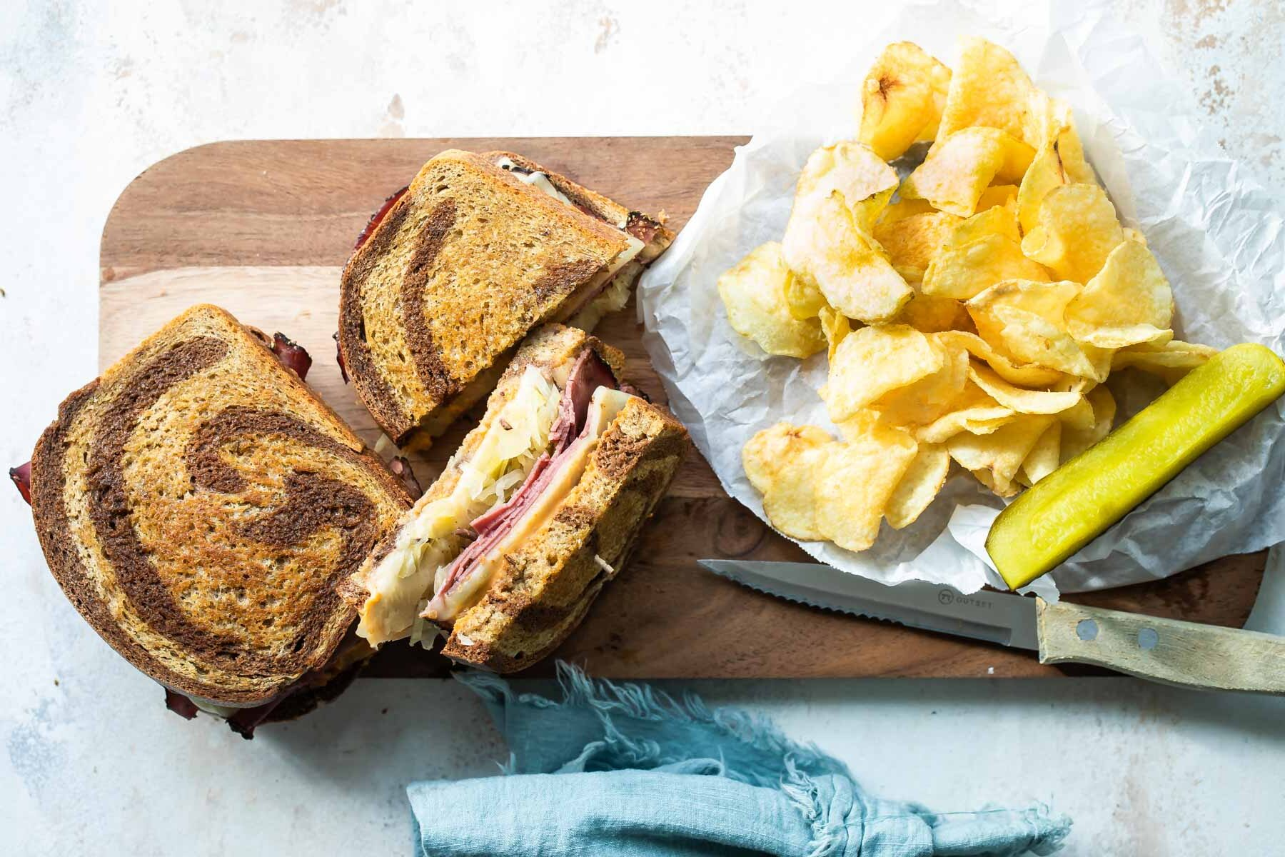 A reuben sandwich on a cutting board surrounded by chips and a pickle spear.