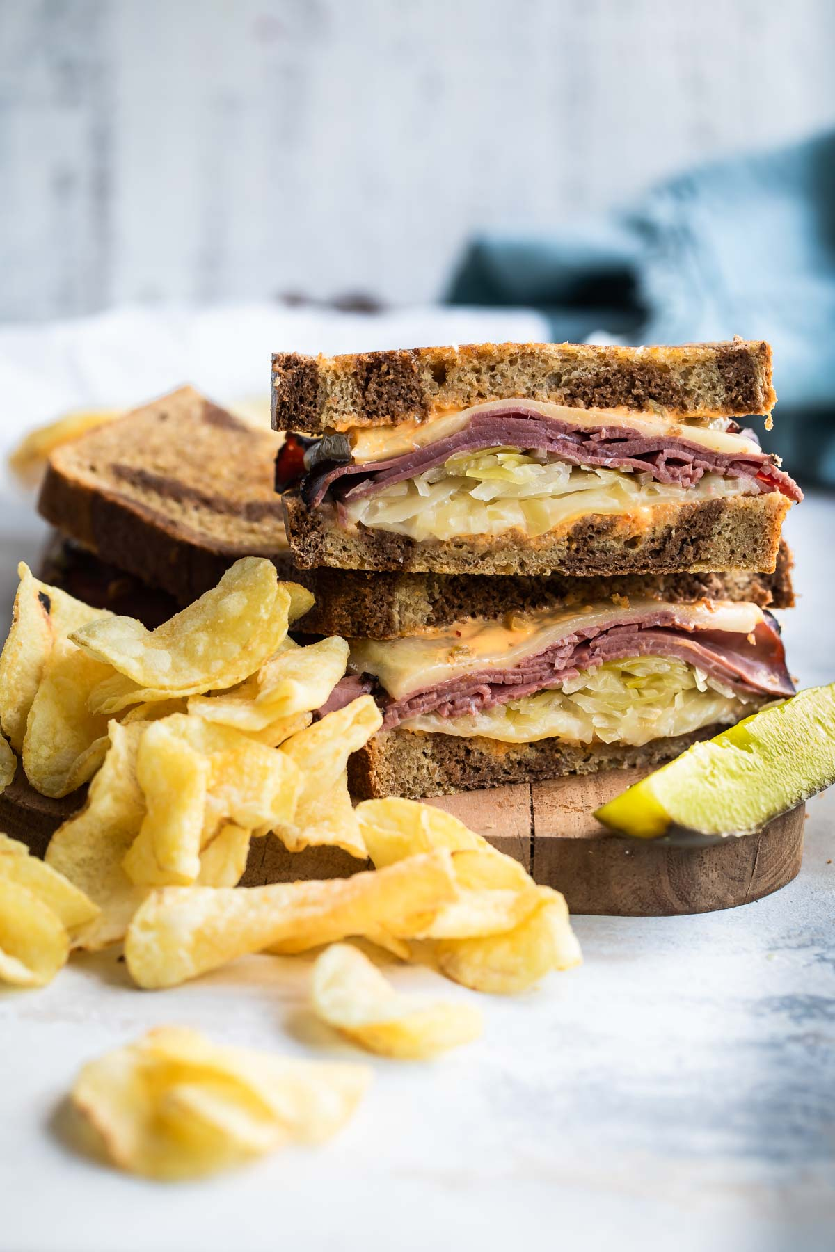 A A reuben sandwich on a cutting board surrounded by chips and a pickle spear.