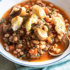 Sausage and bean stew in white bowls.