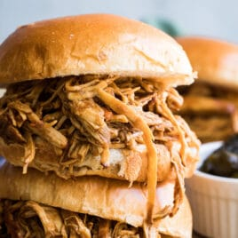 Two pulled chicken sandwiches stacked on top of each other on a baking sheet.