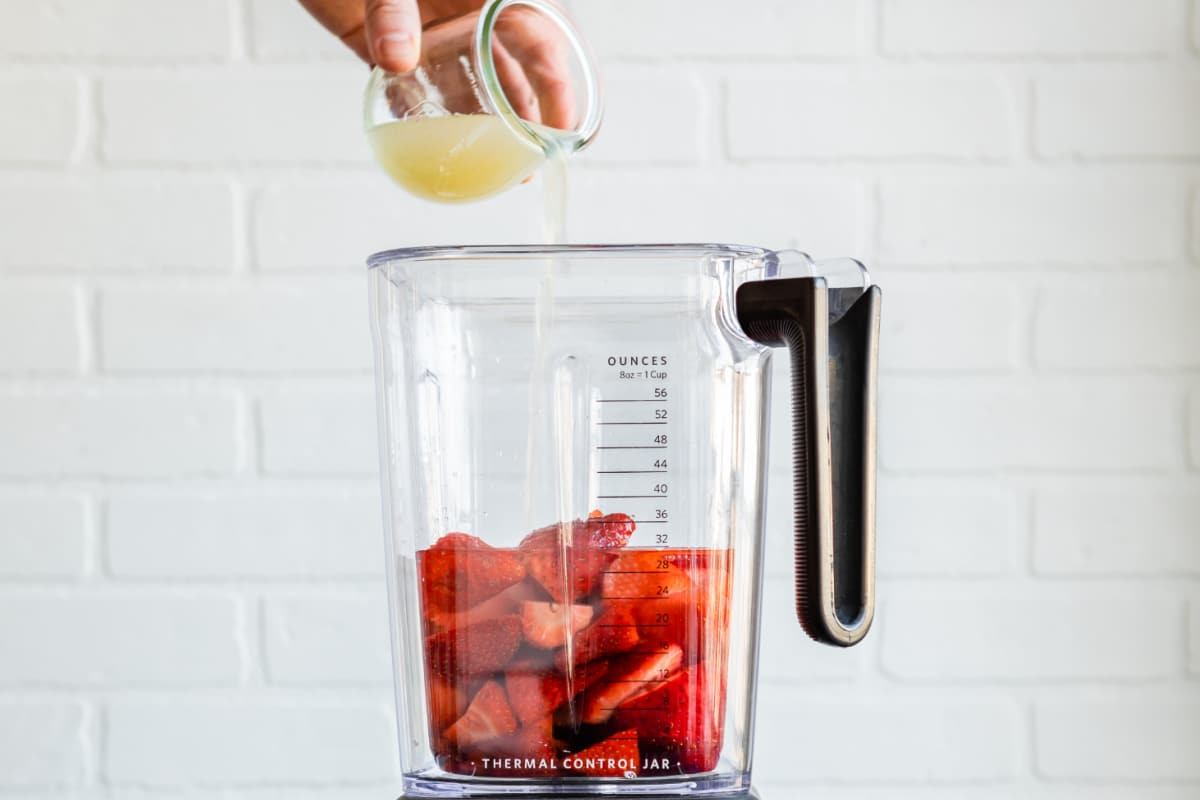 Strawberry margarita ingredients in a blender.