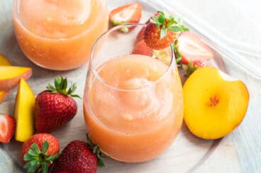 Two glasses of strawberry peach frose on a plate surrounded by slices of strawberries and peaches.