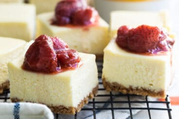 Cheesecake squares topped with strawberry topping on a cooling rack.