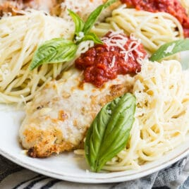 Chicken parmesan on a white serving platter.