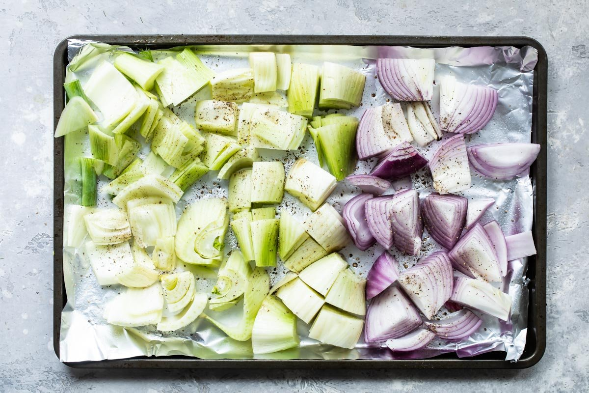 Uncooked fennel and onions on a baking sheet.