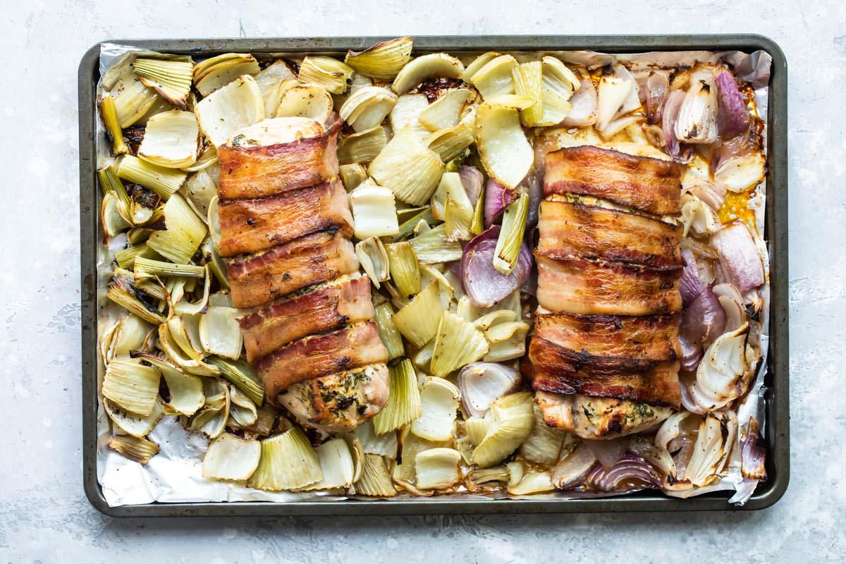 Baked bacon wrapped pork tenderloin on a baking sheet with roasted fennel and onions.