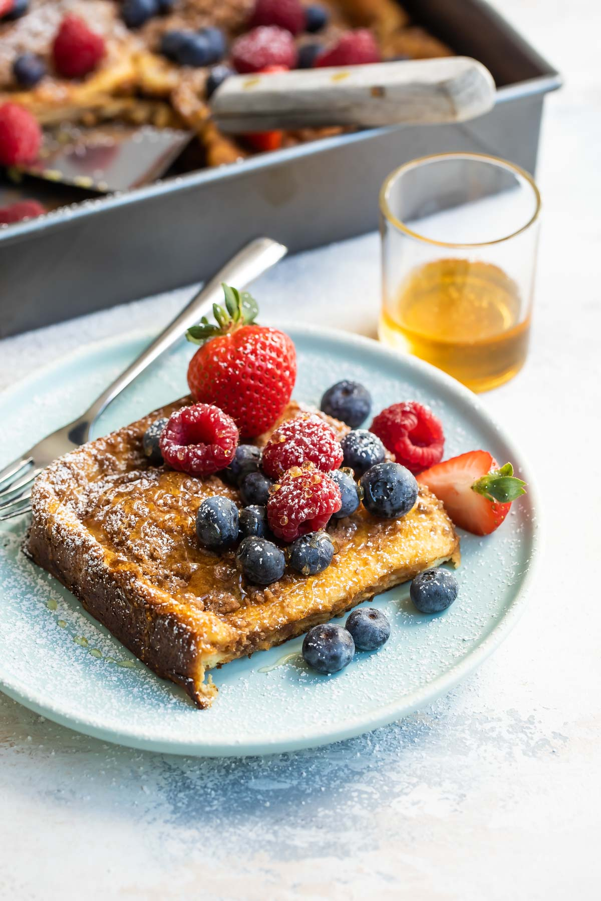 Baked french toast on a plate covered with berries.