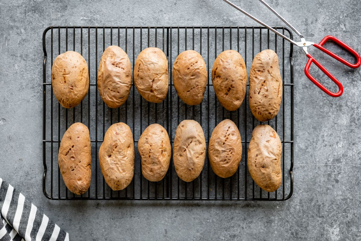 Baked potatoes cooling on a rack.