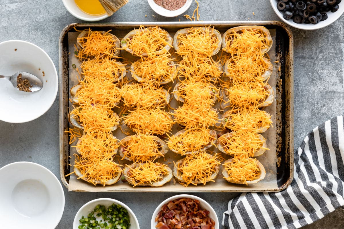 Baked potato halves with meat and cheese.