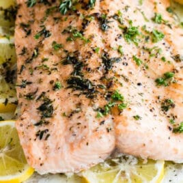 Baked salmon on a bed of lemon slices with fresh herbs.