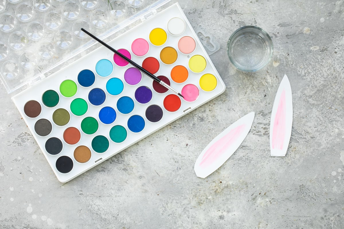A pallet of water colors, a clear glass with water, and painted bunny ears.