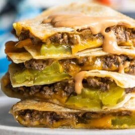 A cheeseburger quesadilla stacked on a plate with a wedge salad in the background.
