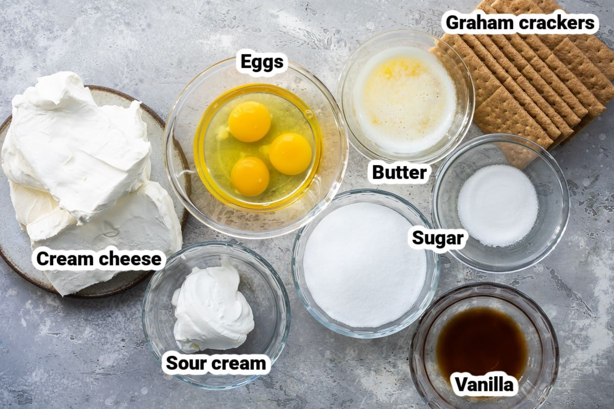 Labeled cheesecake bar ingredients in various bowls.