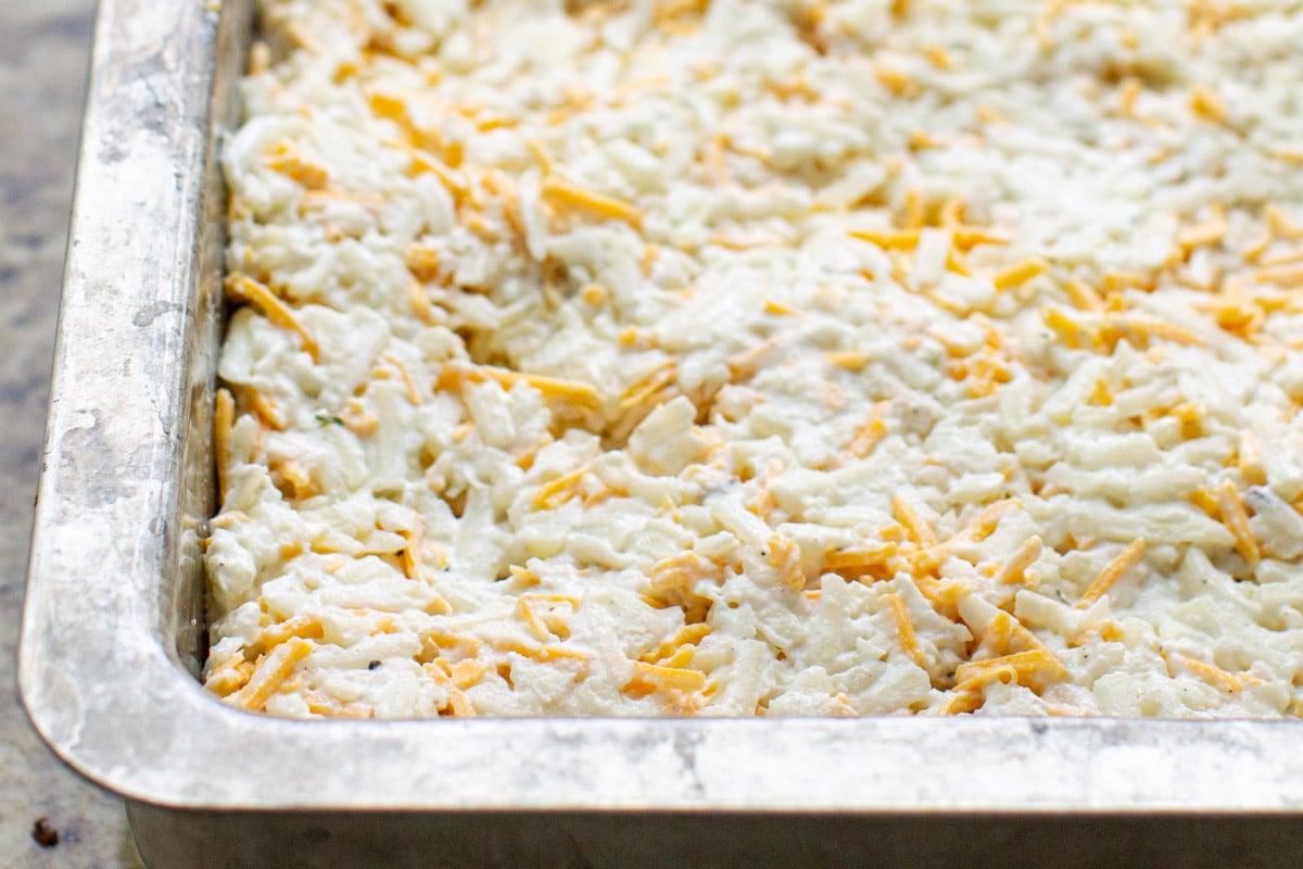 Cheesy potato casserole in a baking dish before baking.