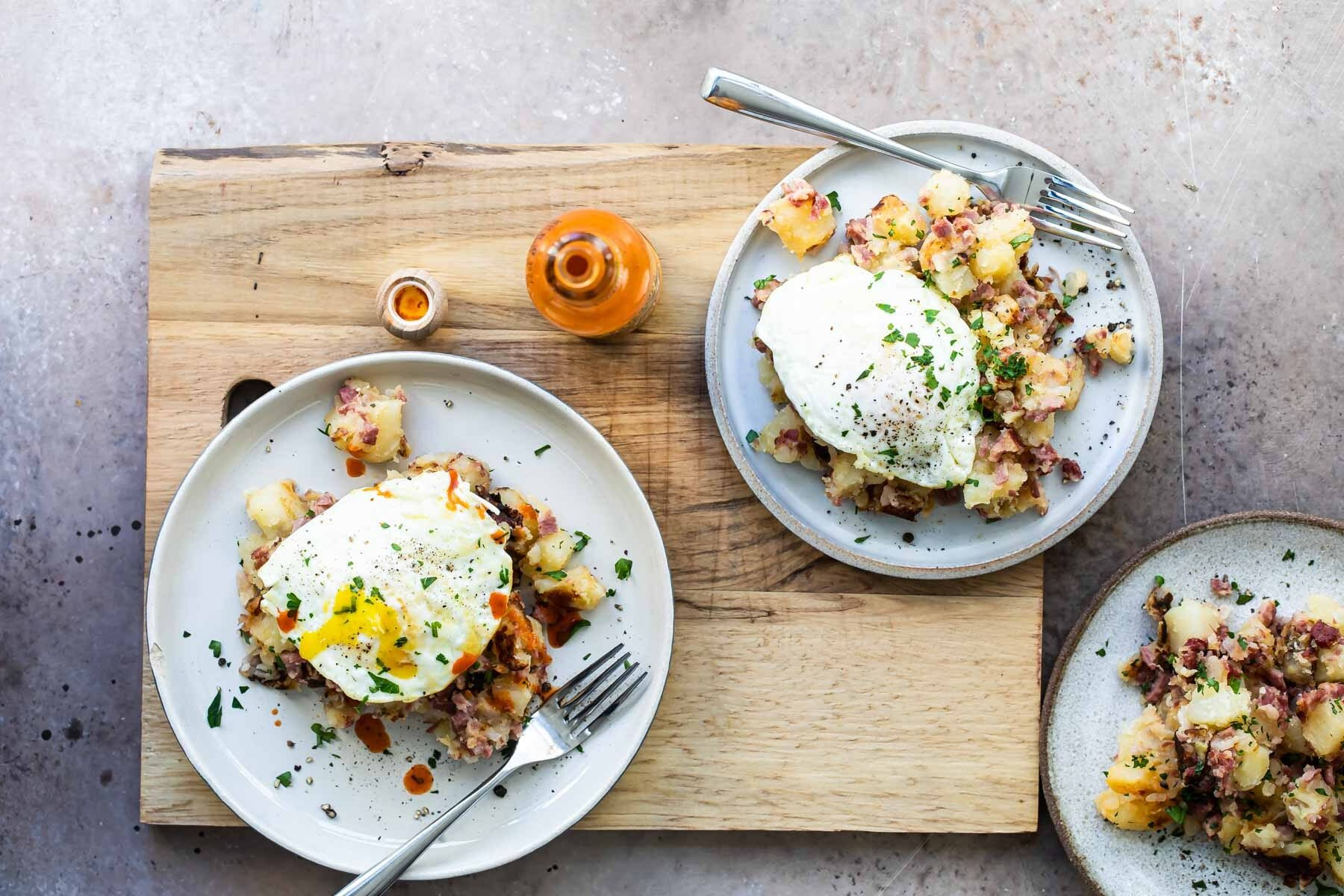 Corned beef hash on a gray plate topped with and egg and parsley.