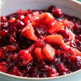 A bowl of cranberry sauce with apples.