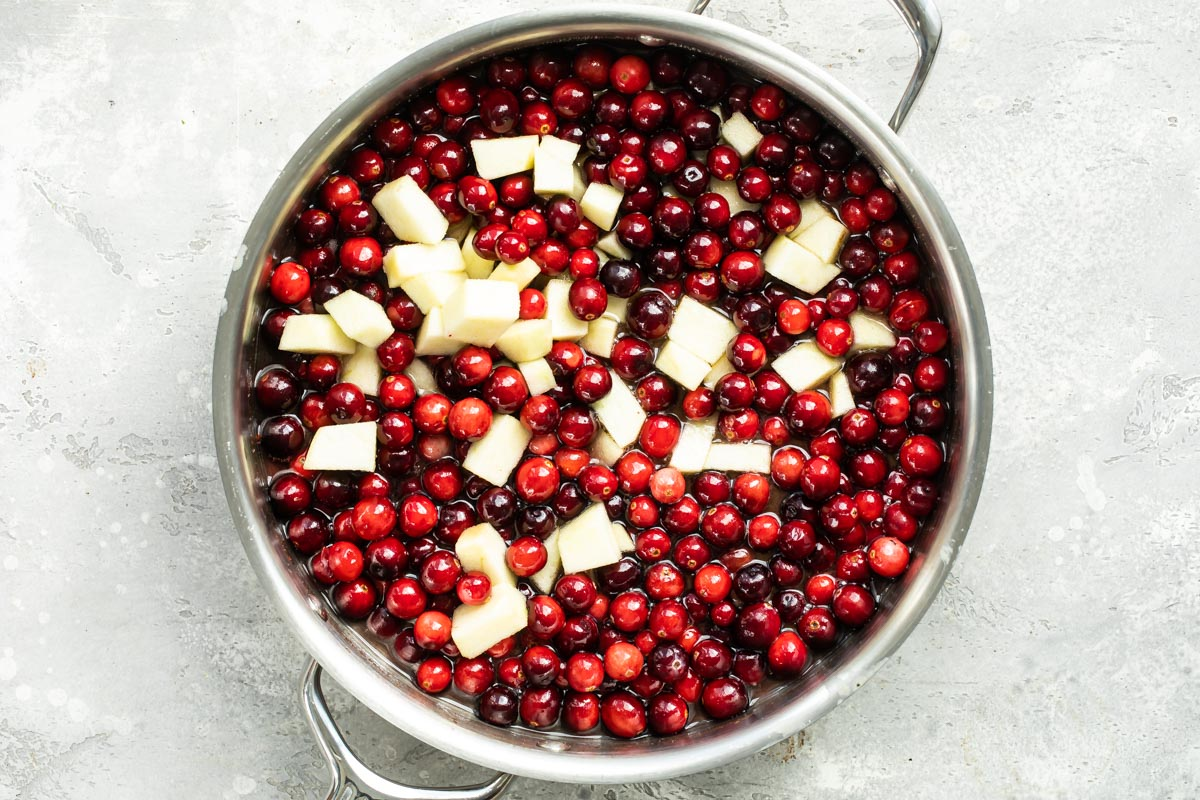 Cranberries and apples cooking in a saucepan.