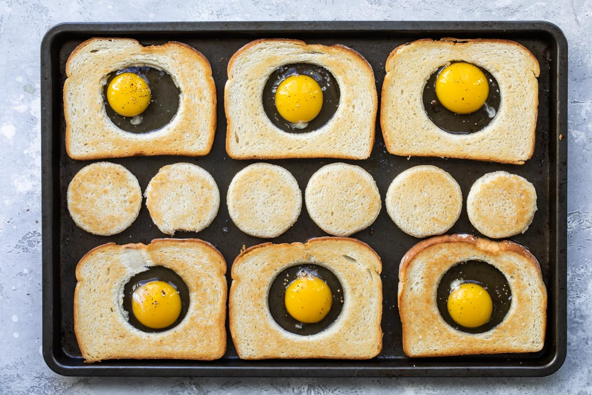 Eggs in a basket cooking on a sheet pan.