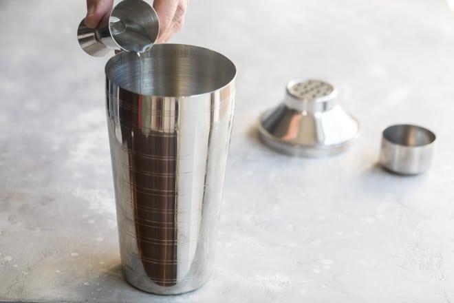 Straining creme de cacao into a martini shaker.