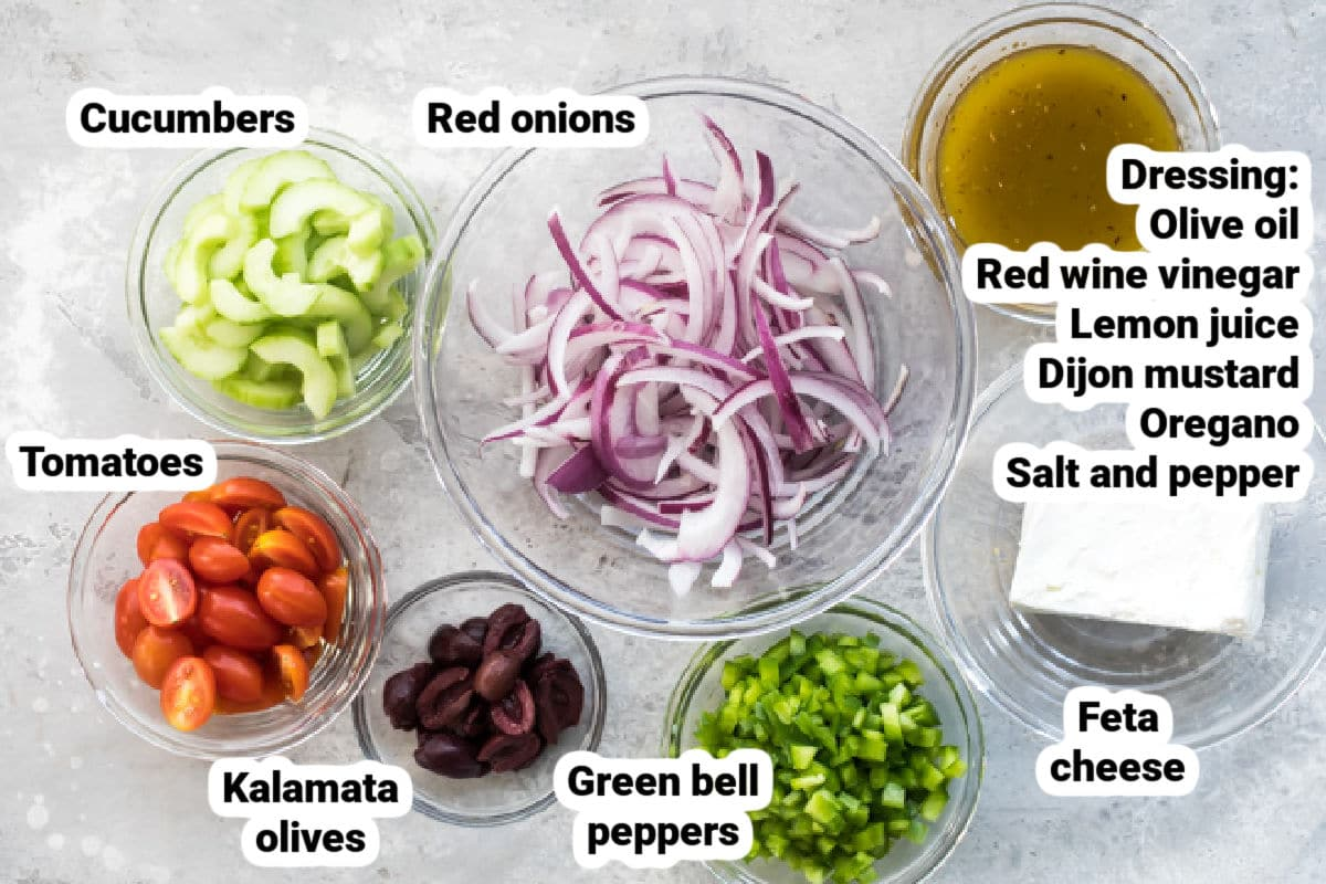 The ingredients for Greek salad in bowls and labeled.
