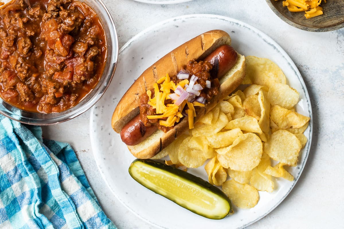 A chili dog on a plate with a pickle and chips.