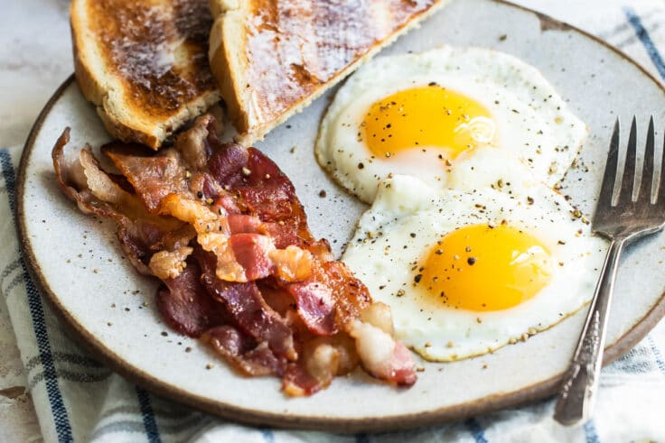 Sunny side up eggs on a plate with bacon and toast.