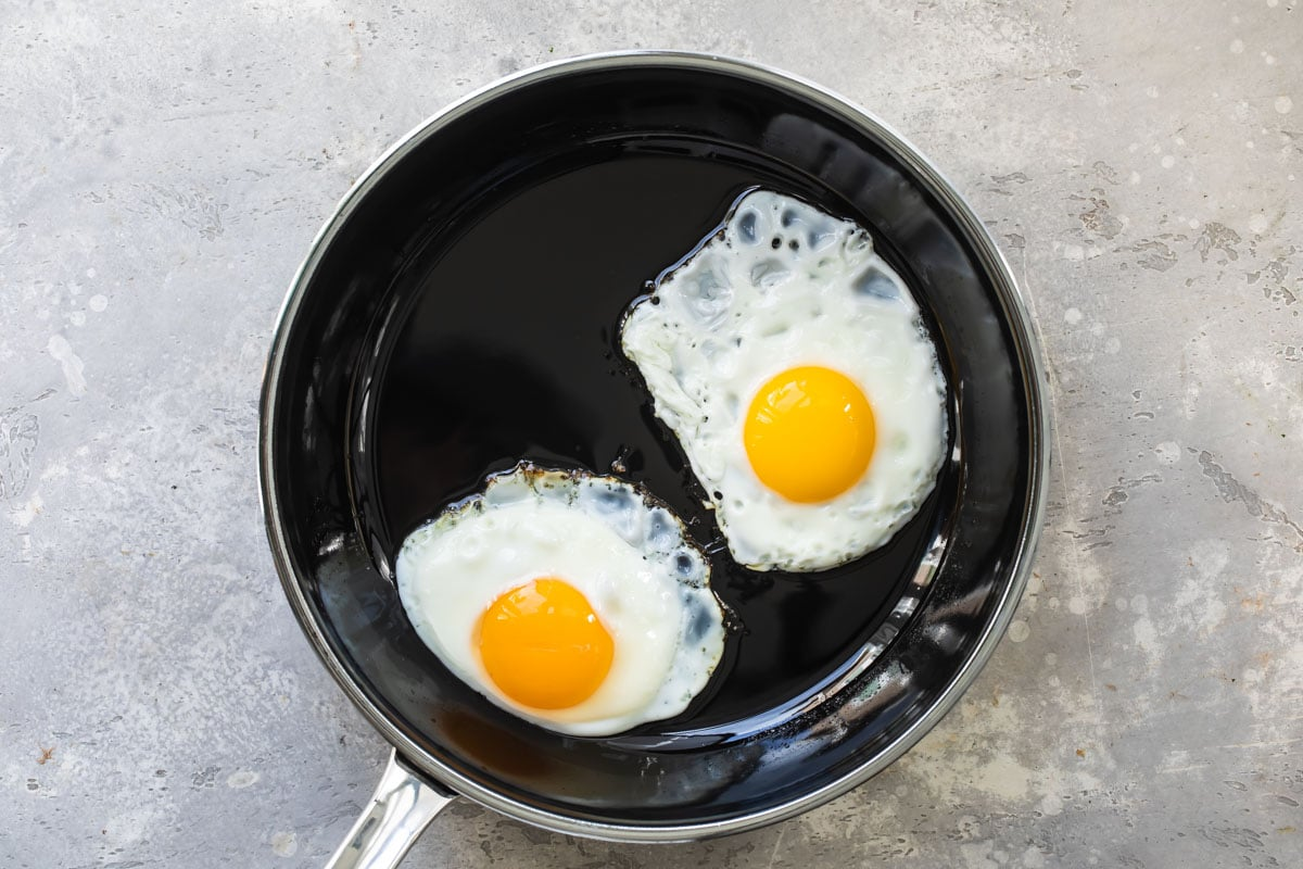 Eggs sunny side up in a skillet.